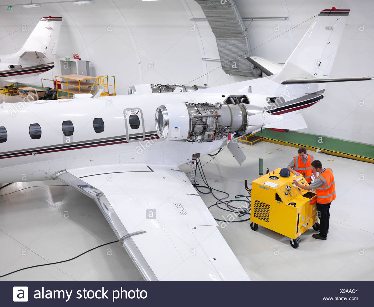 Engineers service a jet aircraft - Stock Image