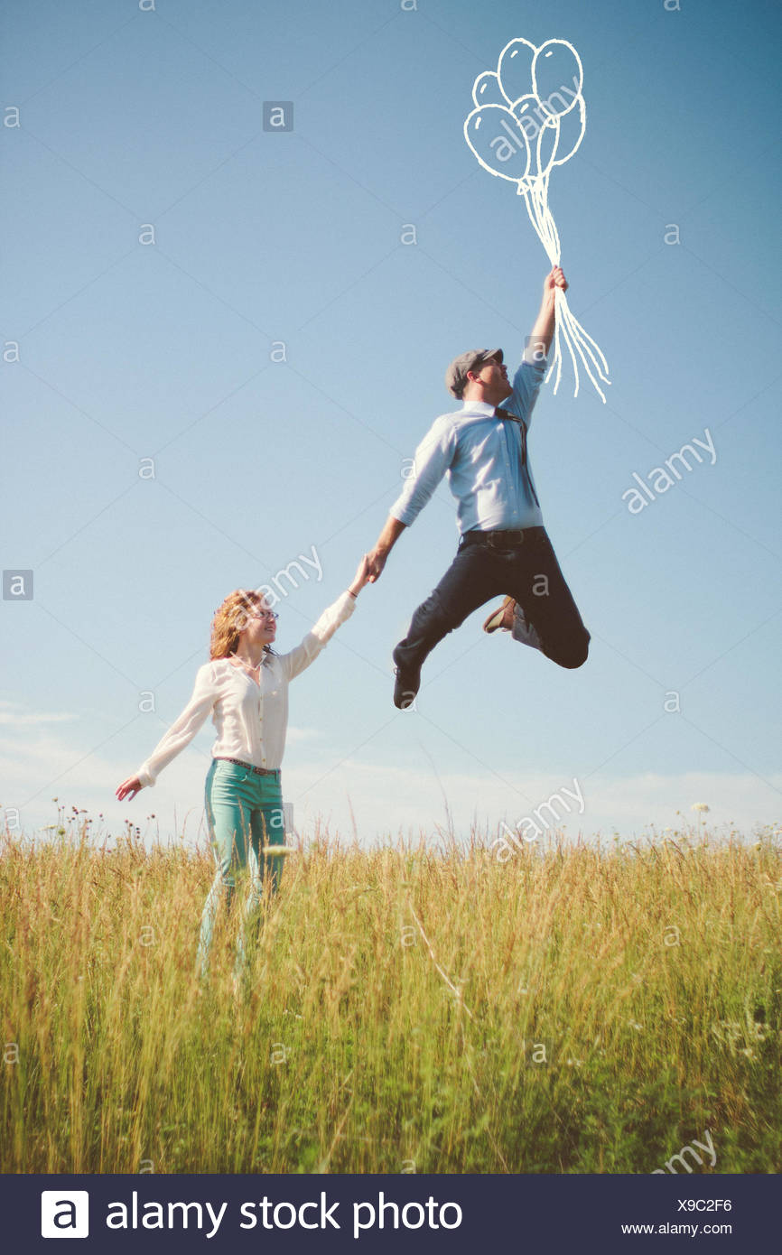 USA, Tennessee, Davidson County, Nashville, Couple with abstract balloons on meadow - Stock Image