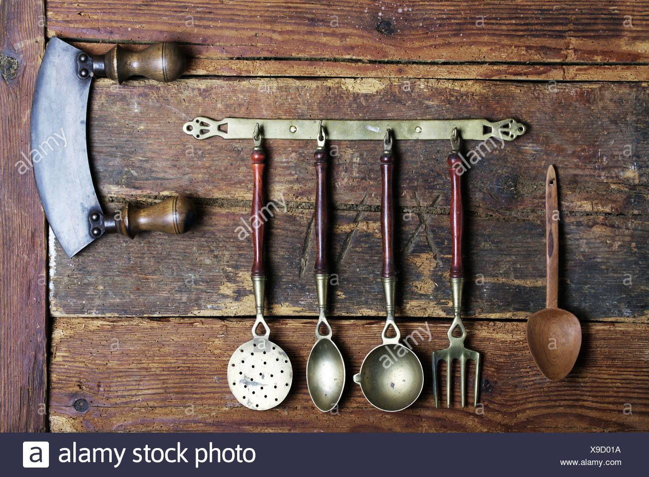 Old Kitchen Utensils Made Of Brass Hanging From A Bar In Front Of A Rustic  Wooden Wall