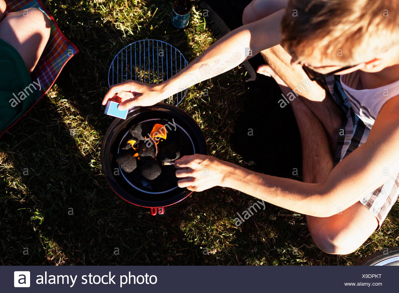 High angle view of man preparing barbeque at picnic - Stock Image