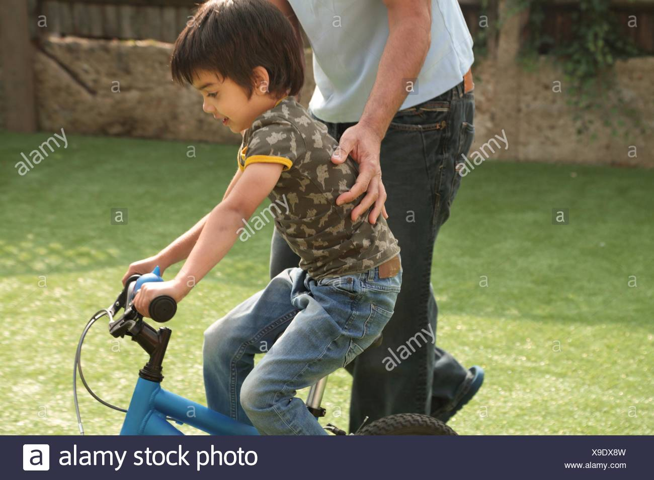 Side view of father supporting boy learning to ride bicycle - Stock Image