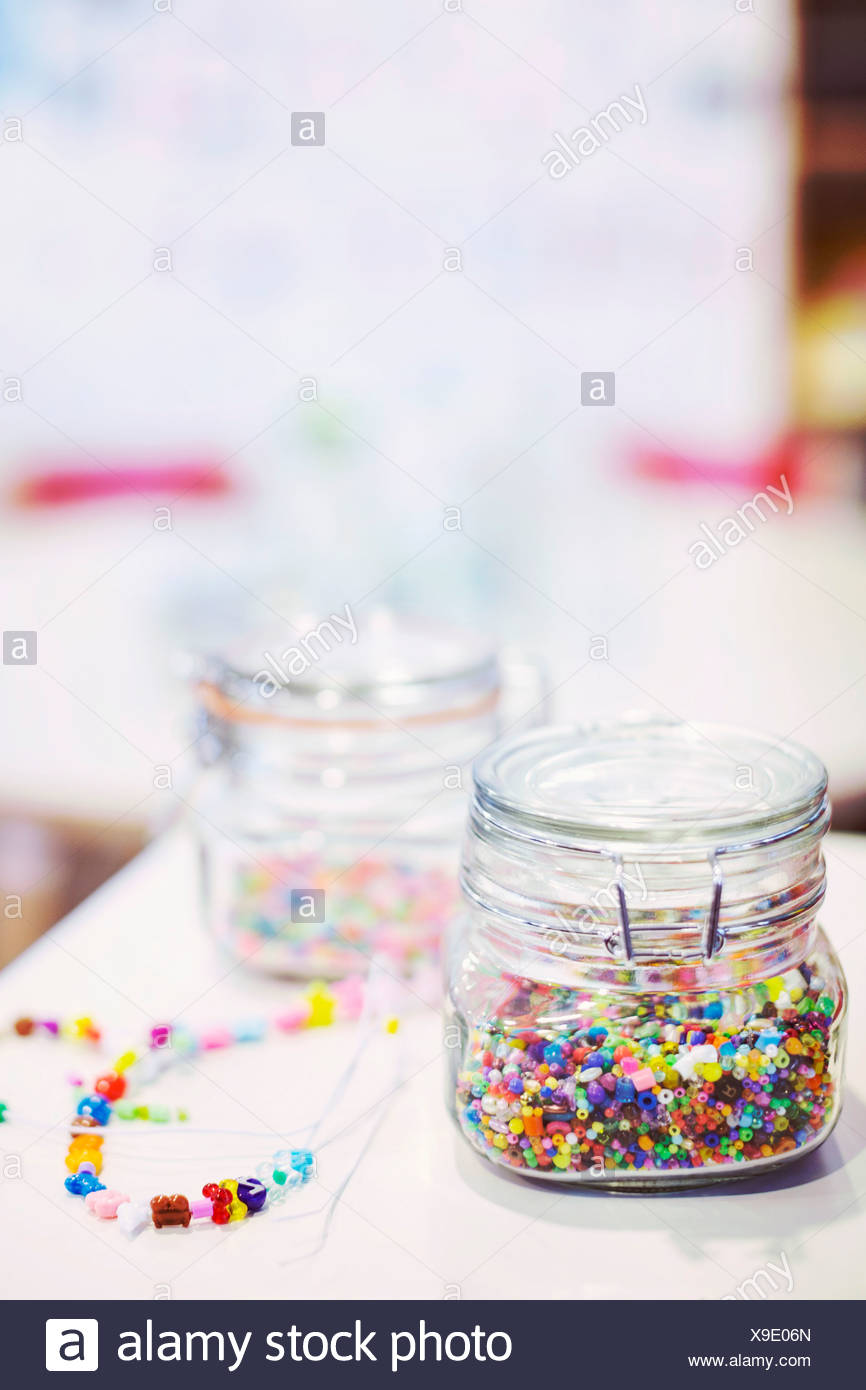 Jars full of beads with necklaces on table in kindergarten - Stock Image