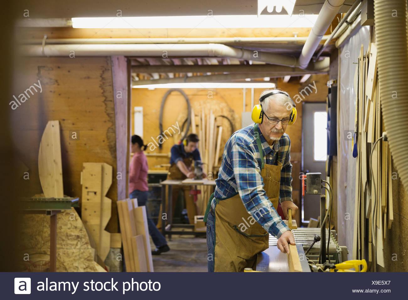 Senior carpenter using equipment in workshop - Stock Image