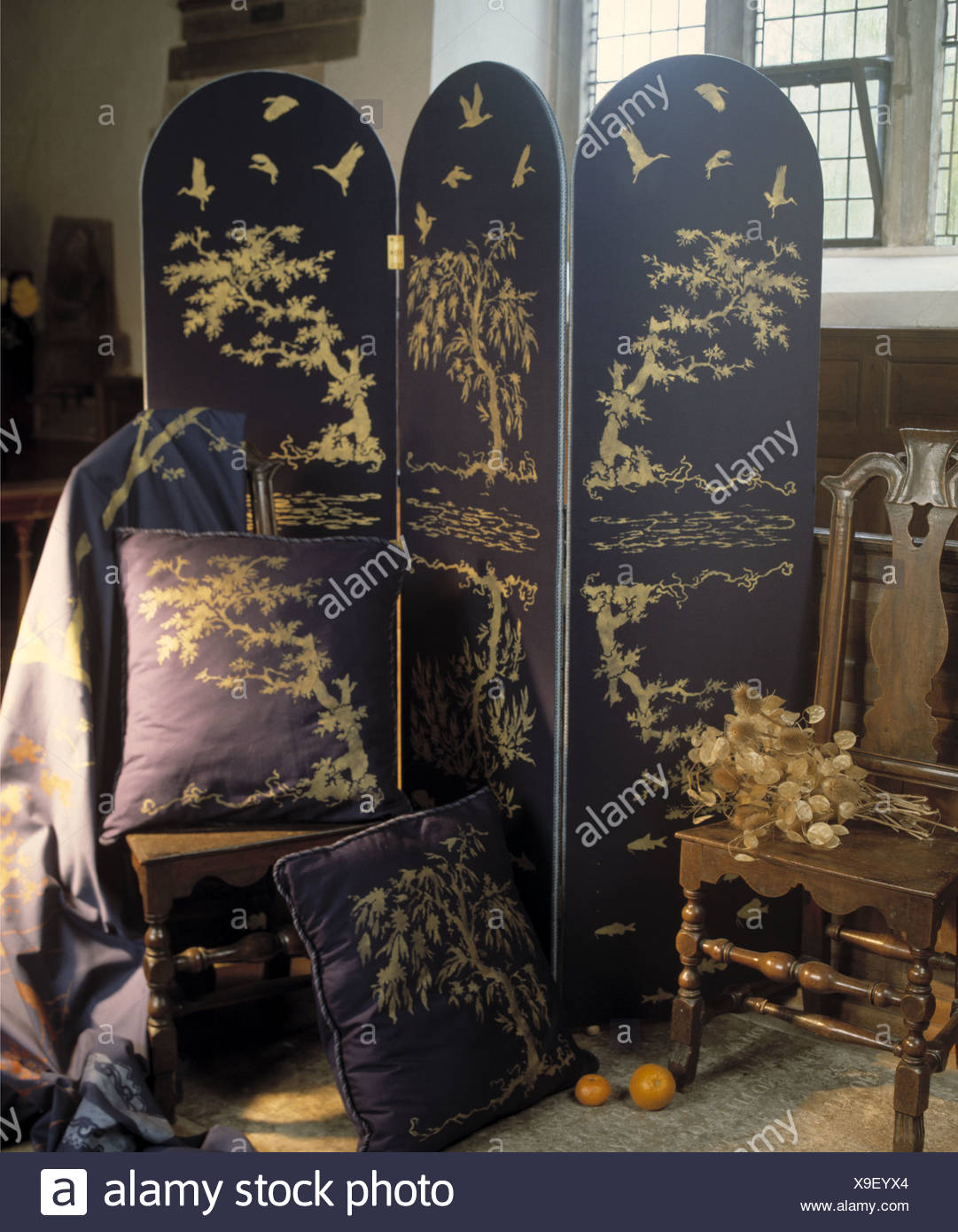 Dark Blue Patterned Folding Screen Beside Matching Cushions And Antique  Chair In Country Dining Room