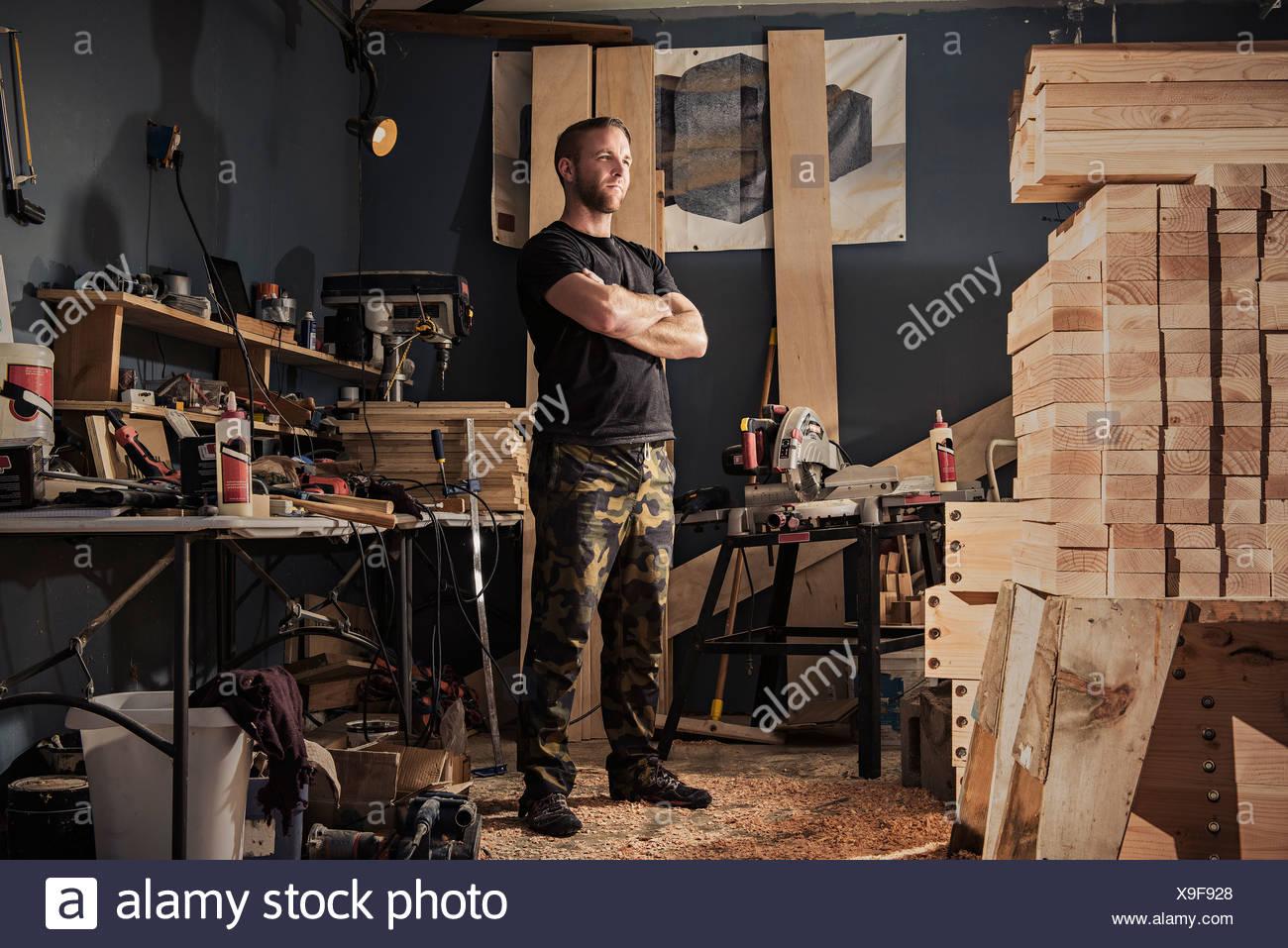 Portrait of mid adult man in carpenter workshop - Stock Image