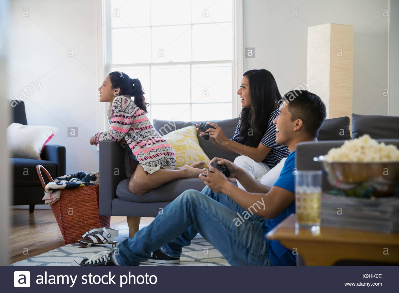 Brother and sisters playing video game living room - Stock Image