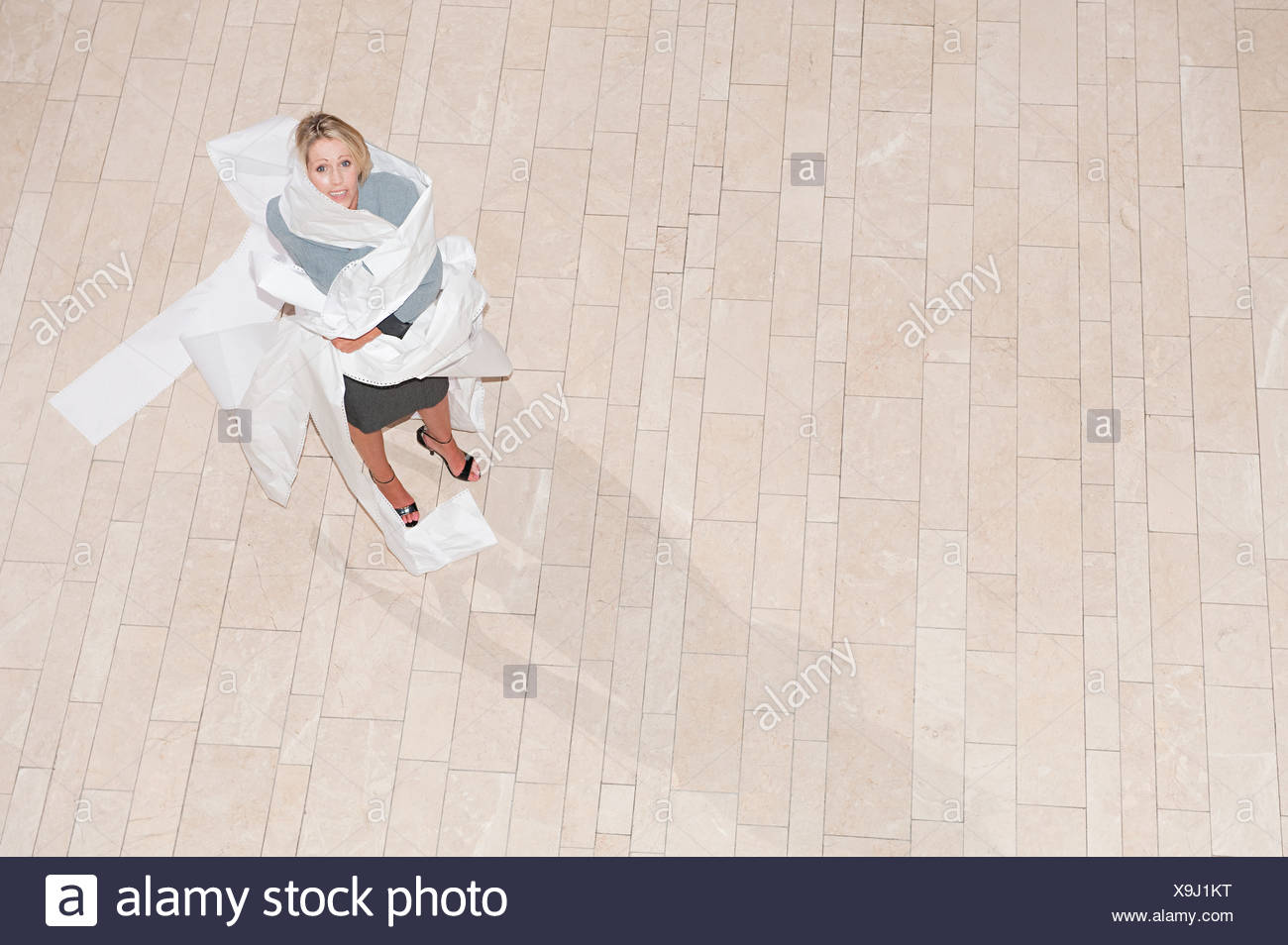 Businesswoman wrapped in printer paper Stock