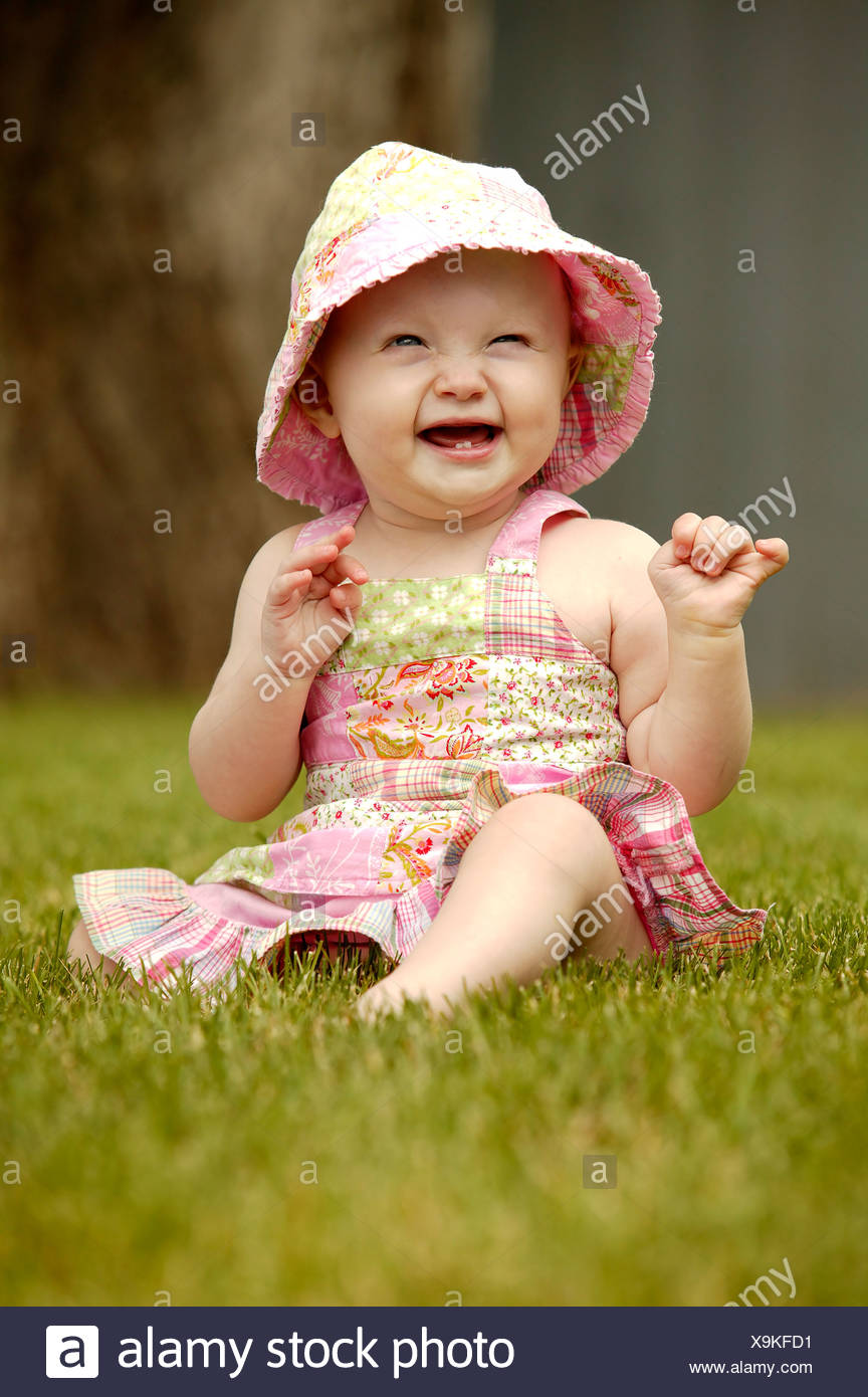 Laughing toddler wearing sunhat, seated on green grass, Saskatechewan, Canada - Stock Image
