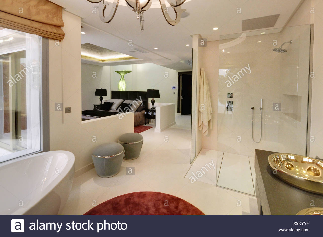large walk in shower and gray stools in open plan en suite bathroom in modern spanish apartment bedroom - En Suite Bathroom