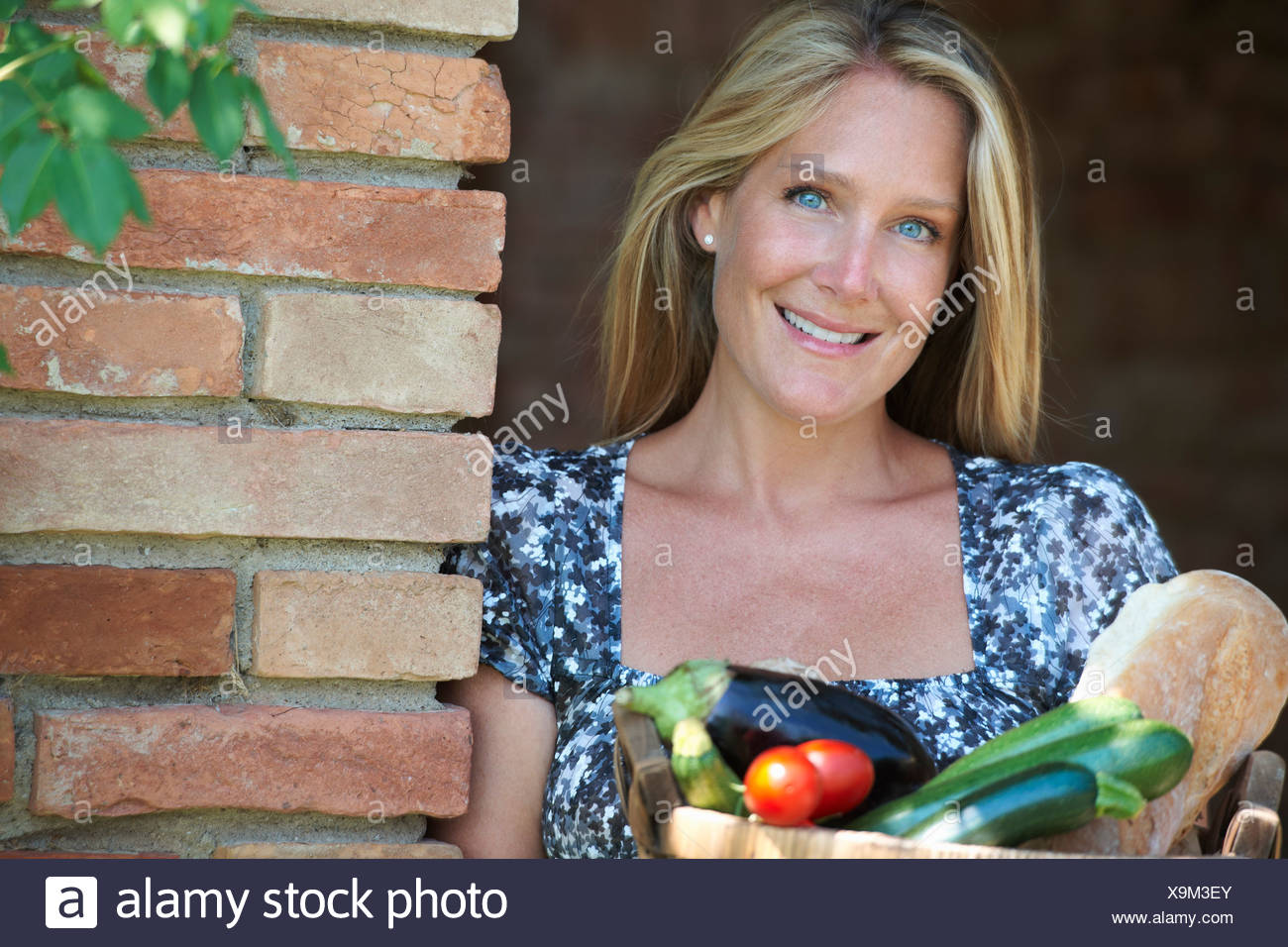 Mature woman standing outside with basket of organic food - Stock Image