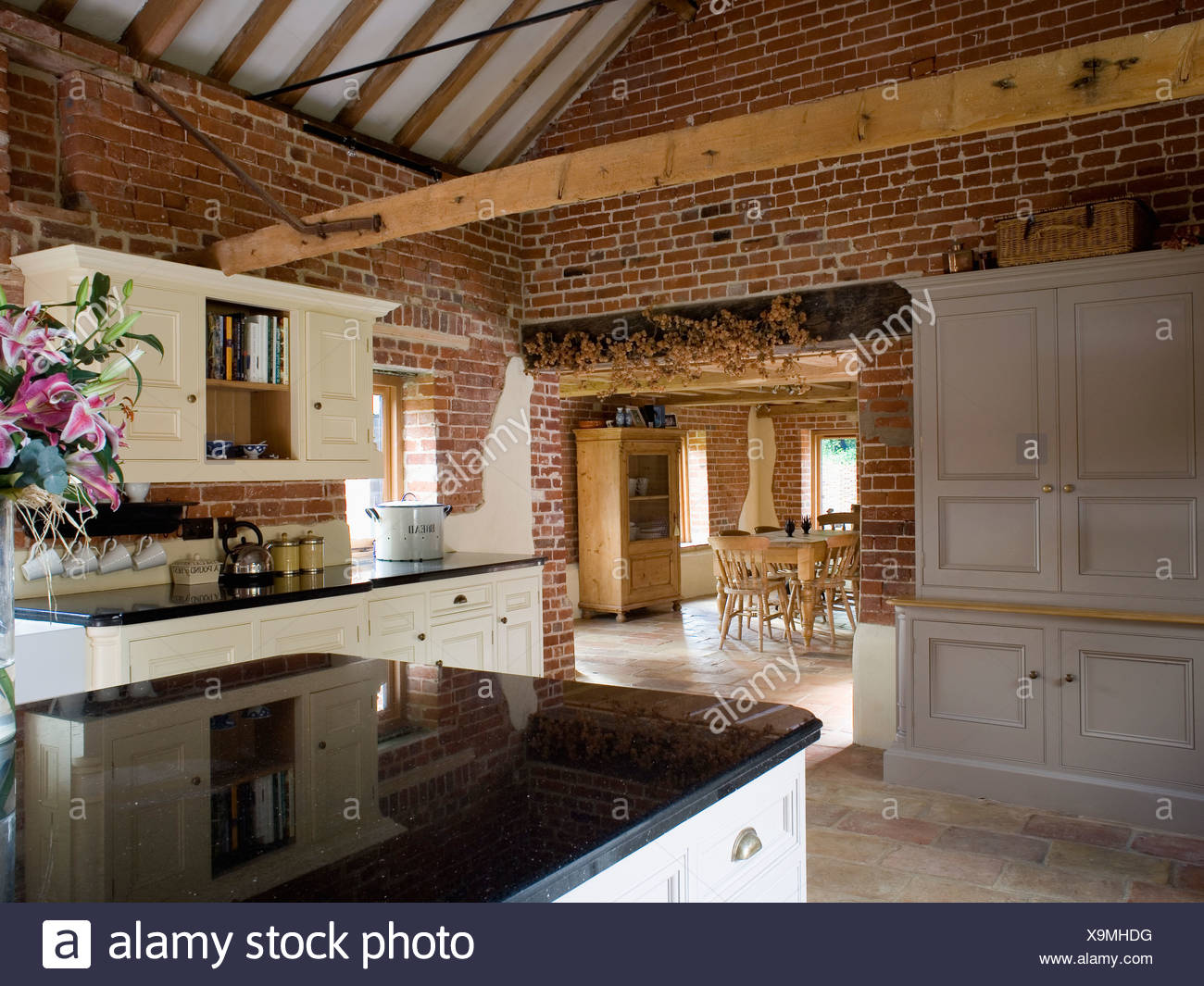 Dresser Beside Open Doorway In Large Barn Conversion Kitchen With Exposed  Brick Walls And Wooden Ceiling Beams