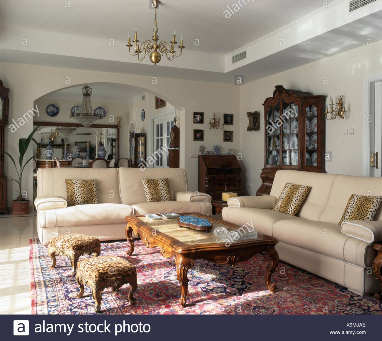 Cream Sofas And Leopard Print Cushions And Stools In Spanish Living Room