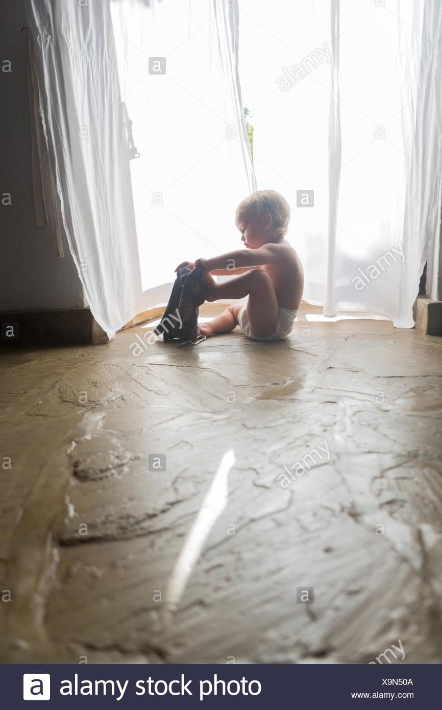Toddler dressing himself in Kenya - Stock Image