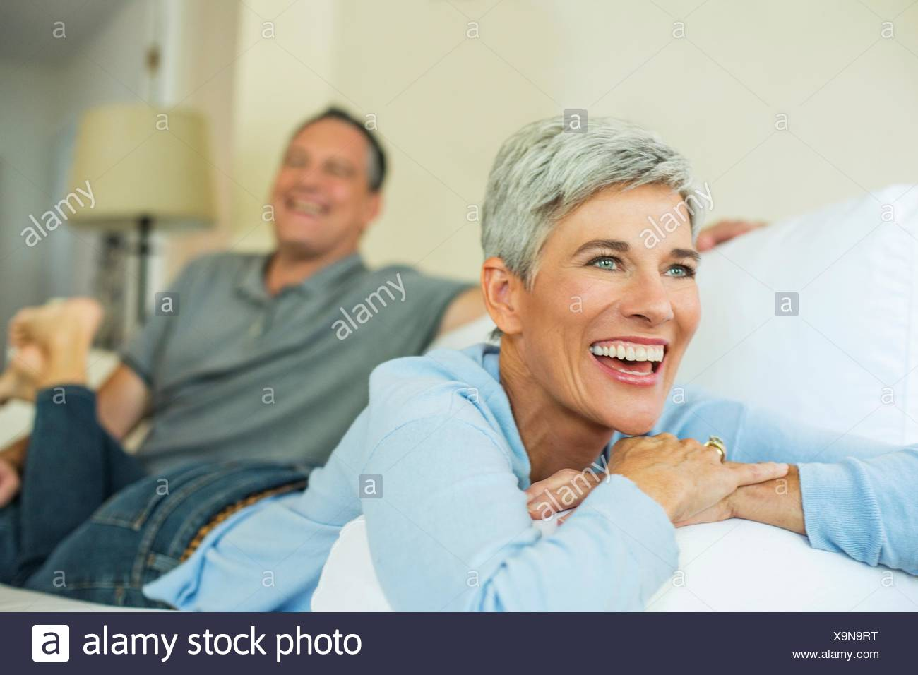 Mature couple laughing and relaxing on sofa - Stock Image