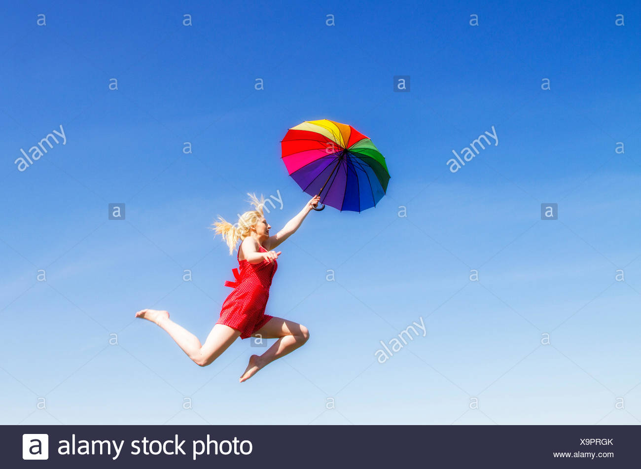 Young woman jumping with colorful umbrella - Stock Image