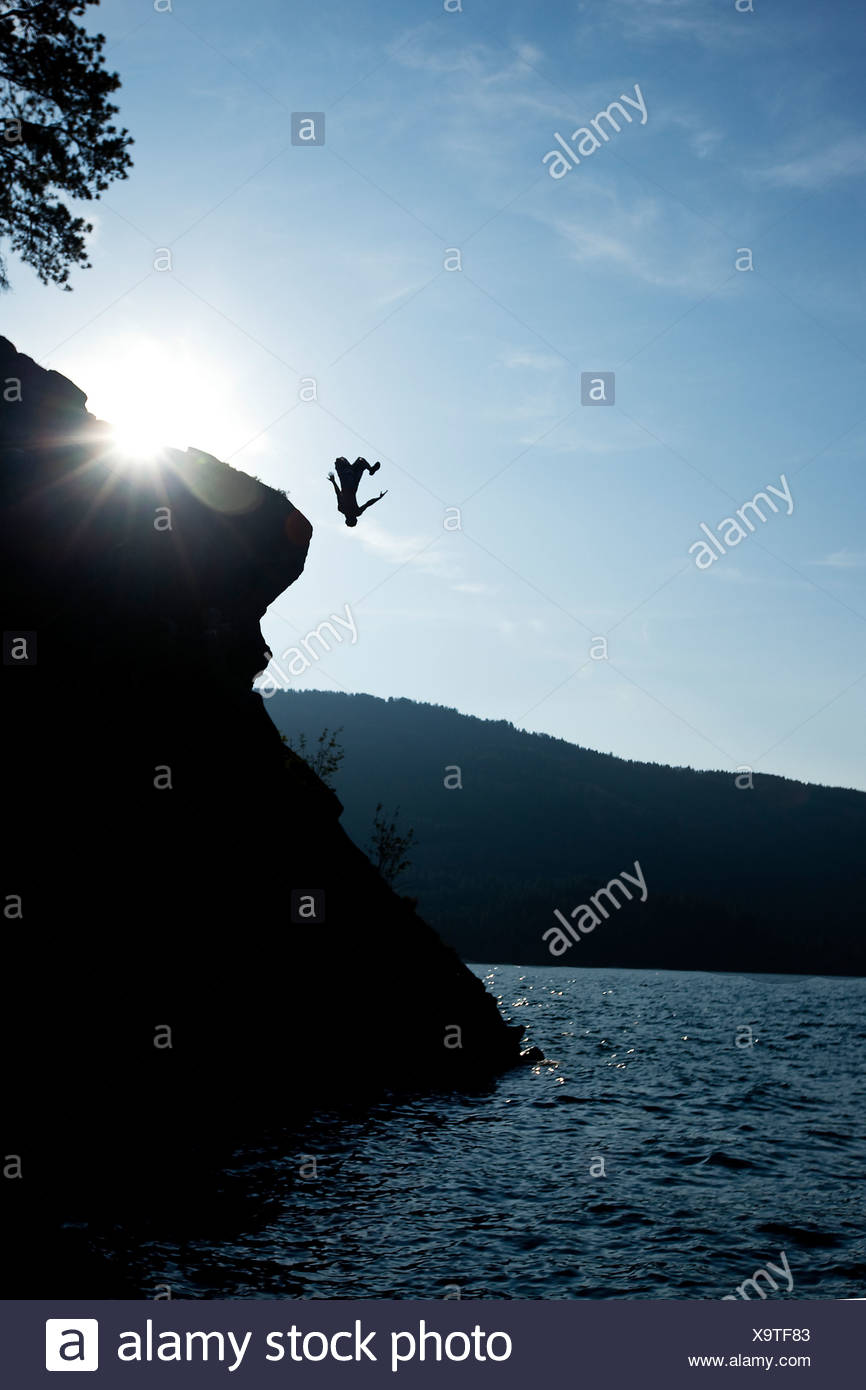 A young man flips off a rock outcropping in Idaho. - Stock Image