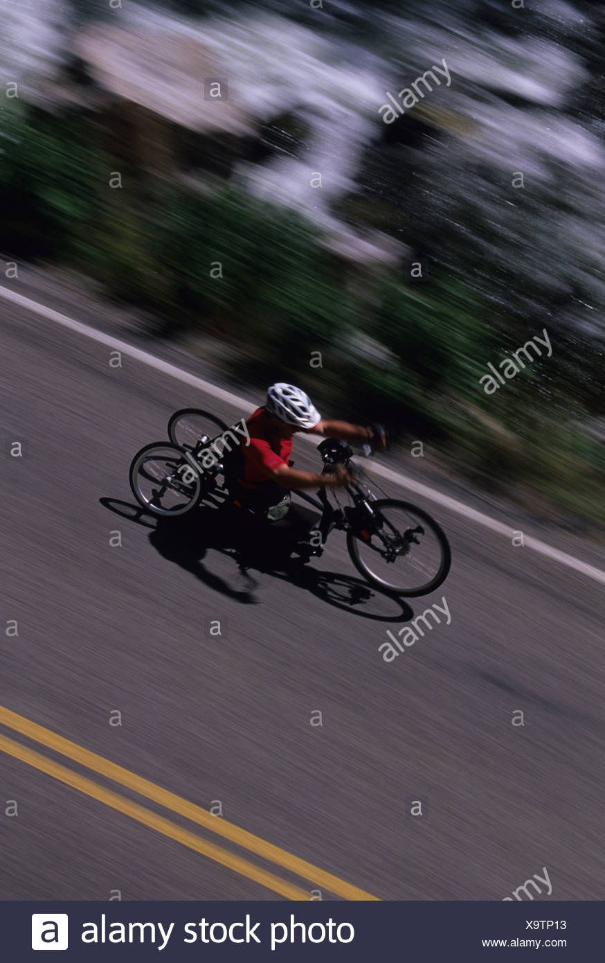 A young athlete with disabilities rides his hand road cycle. - Stock Image