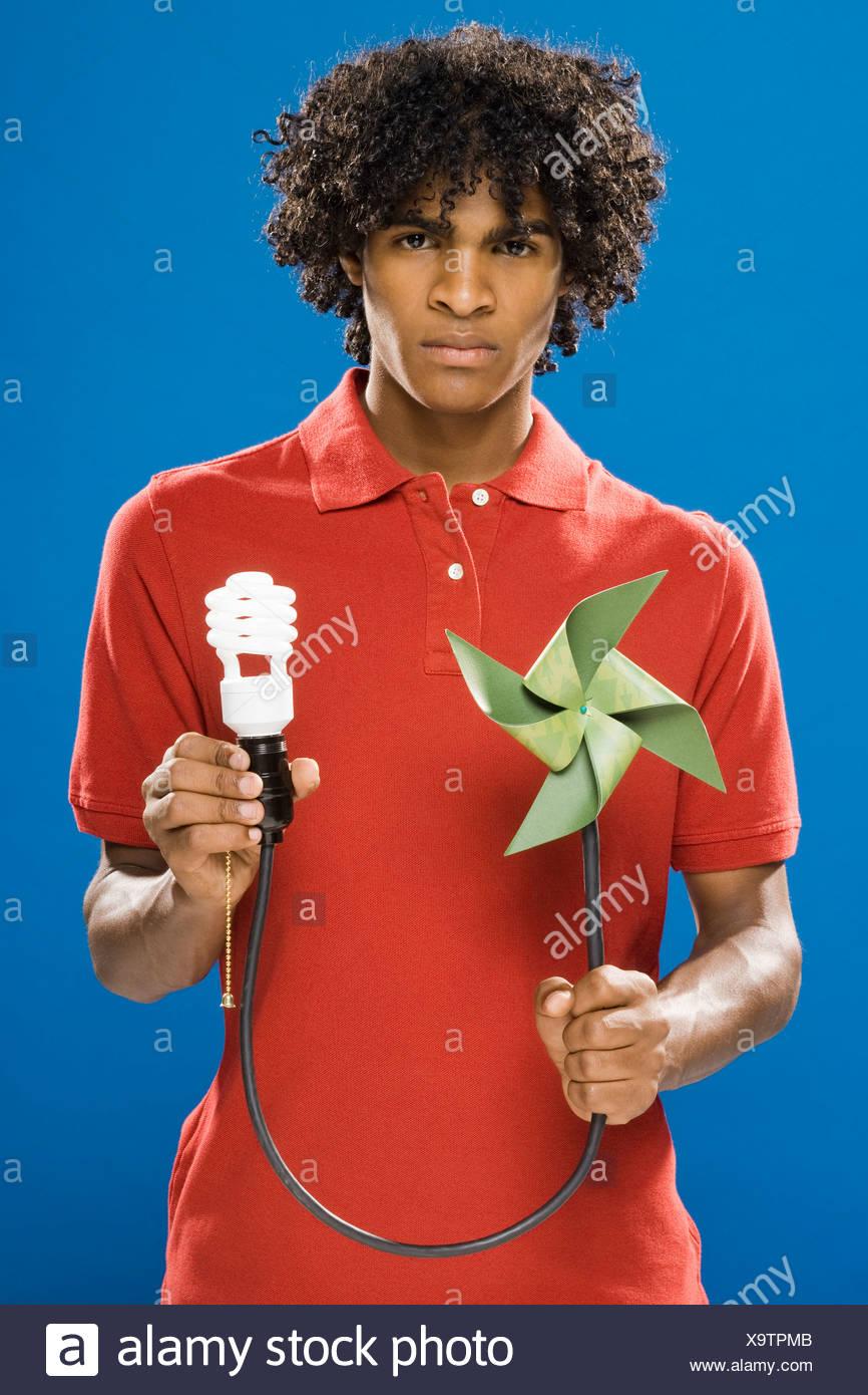 young man with pinwheel and energy saving light bulb - Stock Image