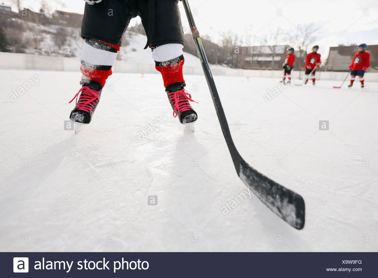 Low section of ice hockey player on rink - Stock Image