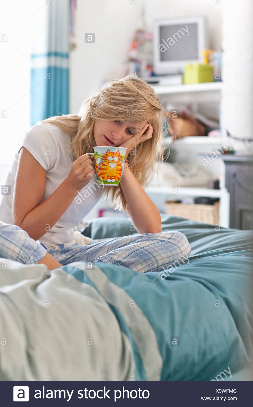 Woman with head in hands sitting on bed with coffee cup - Stock Image
