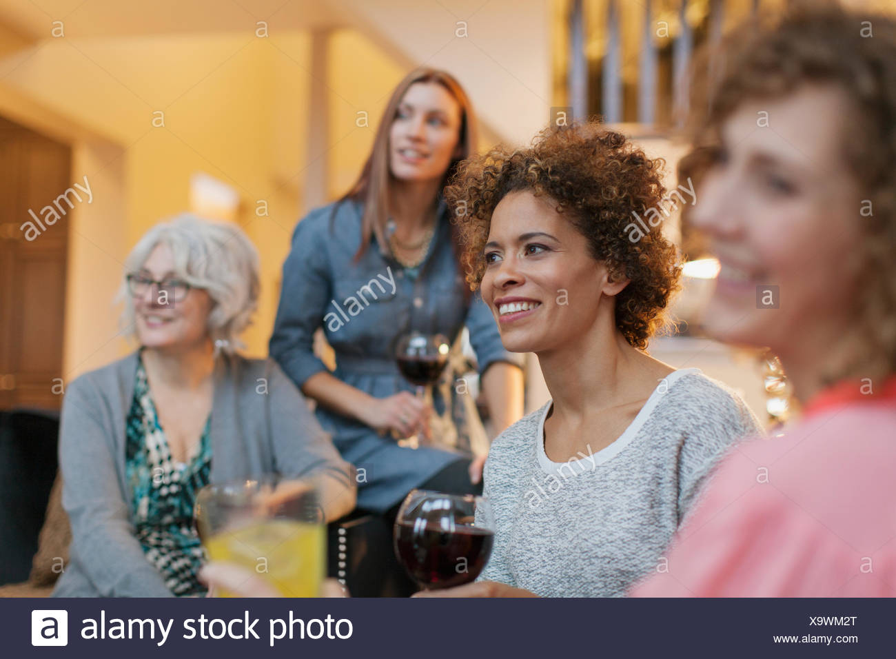 Girlfriends enjoying some wine at home. - Stock Image