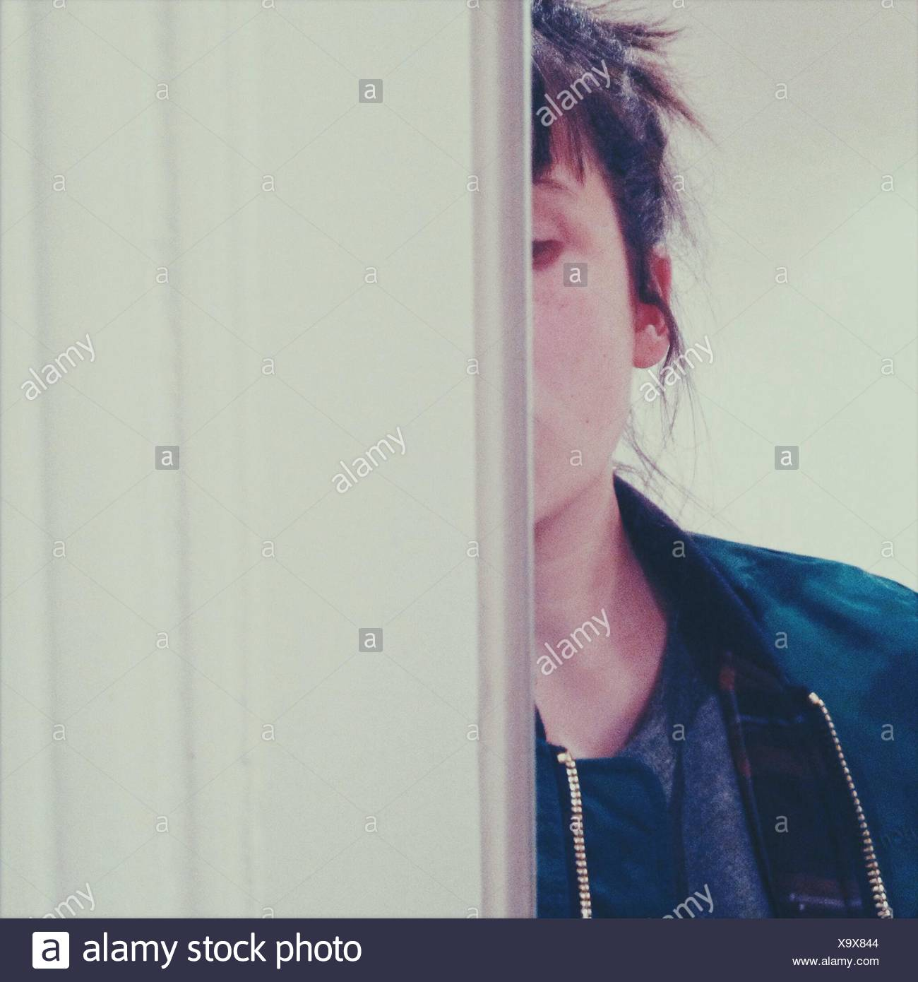 Cropped Image Of Woman Hiding Behind Wall - Stock Image