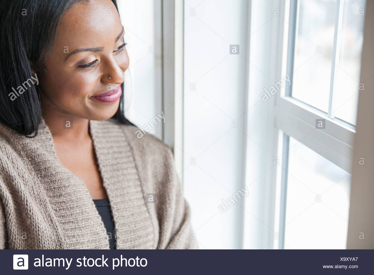 Smiling woman looking out window at home - Stock Image