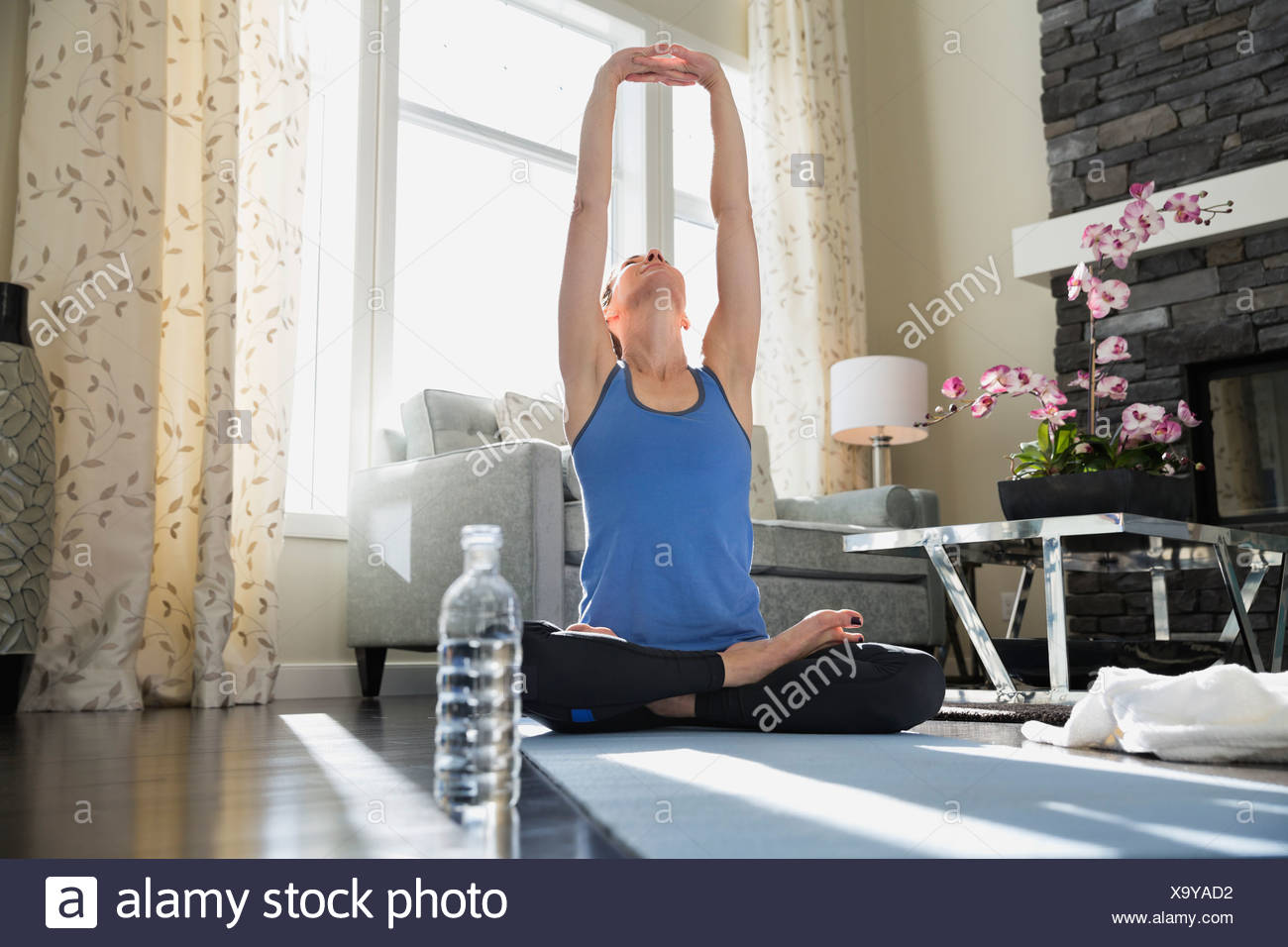 Mature woman with arms raised doing yoga on mat - Stock Image