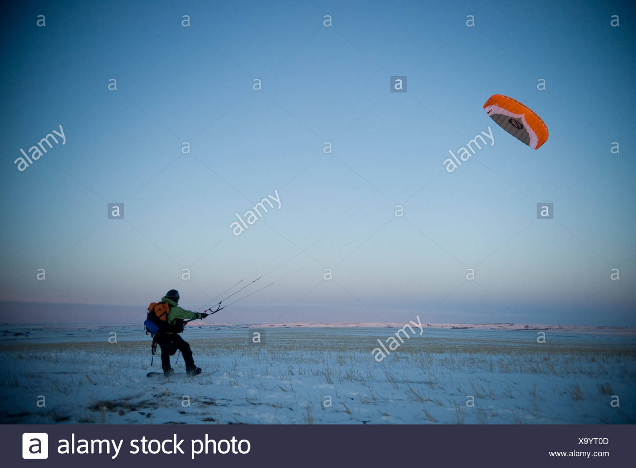 A young man taking off with his snowkite. - Stock Image