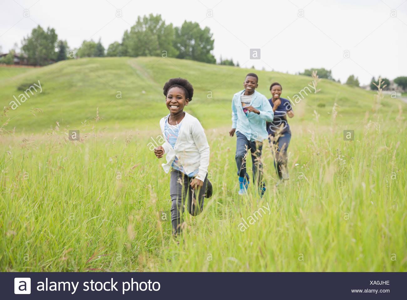 Cheerful siblings running through field - Stock Image