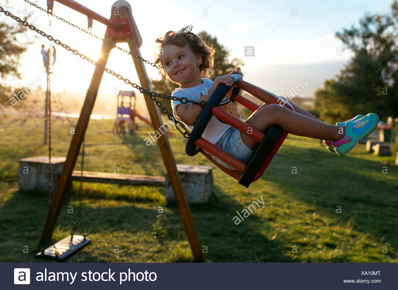 Portrait of happy little girl on a swing at backlight - Stock Image