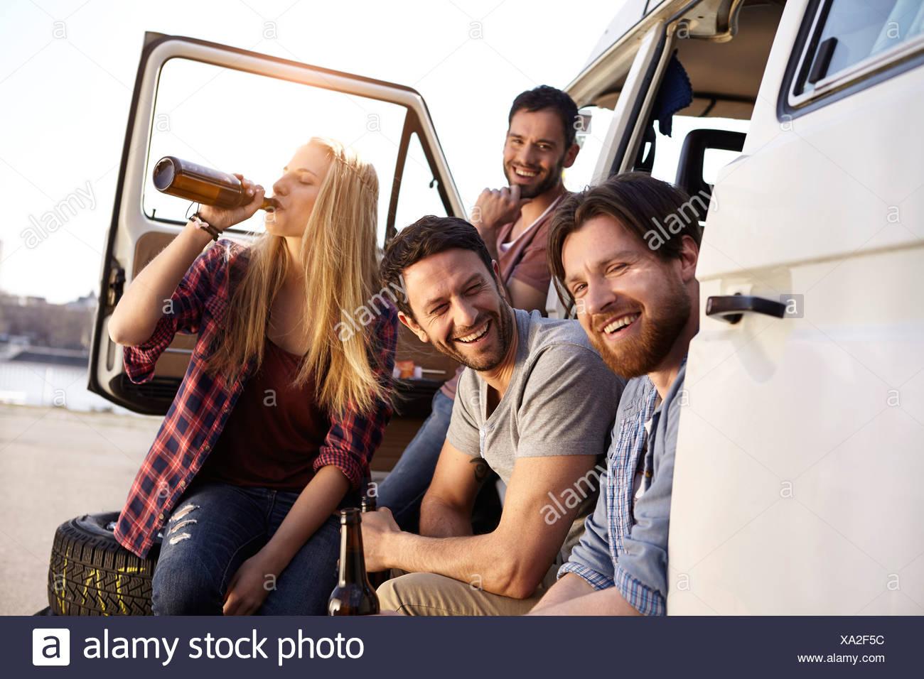 Happy friends celebrating at minivan - Stock Image