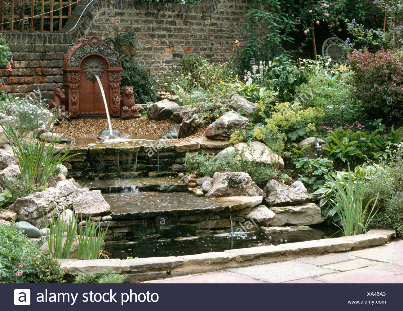 Lion Fountain On Wall Above Waterfall Over Stone Steps Edged With Rocks In A  Walled Country Garden In Summer