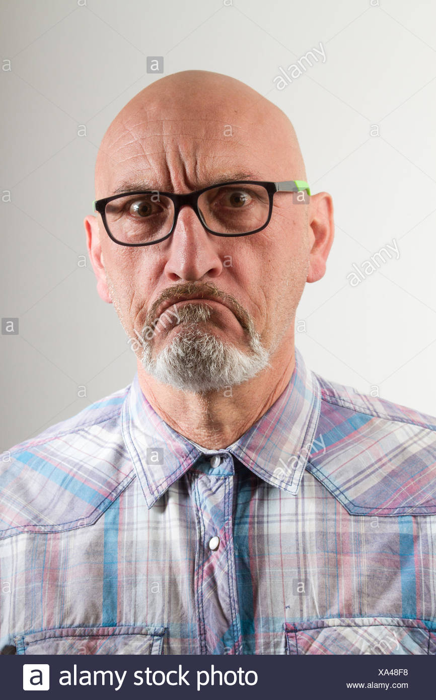 Close-Up Portrait Of Angry Man In Eyeglasses Against Gray Background - Stock Image