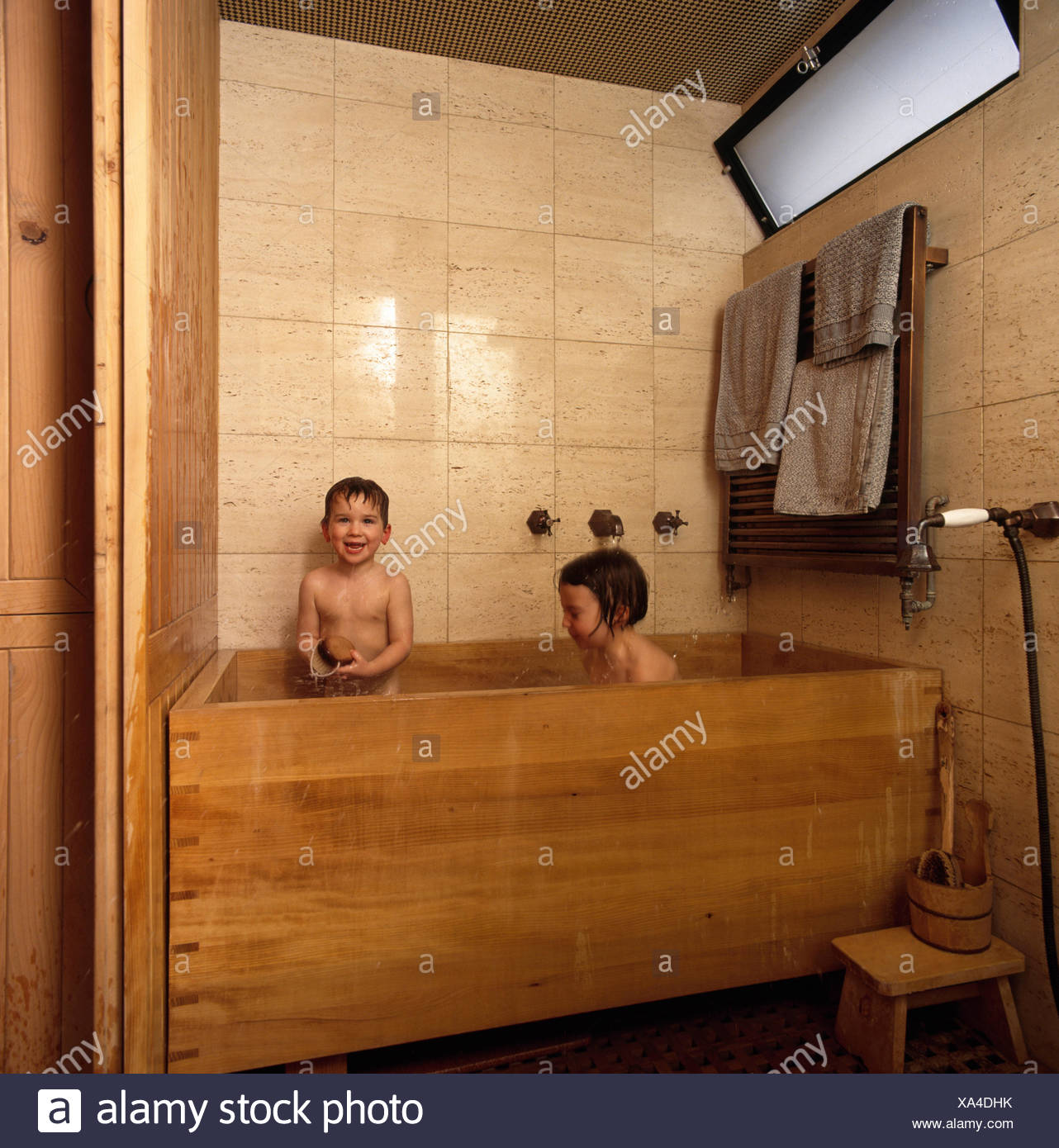 Two small children in a wooden bathtub FOR EDITORIAL USE ONLY Stock ...
