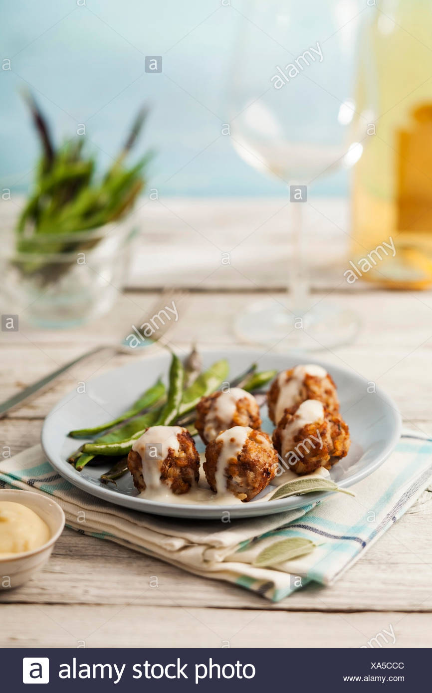 Tasty meatballs in white sauce with sage and green beans - Stock Image