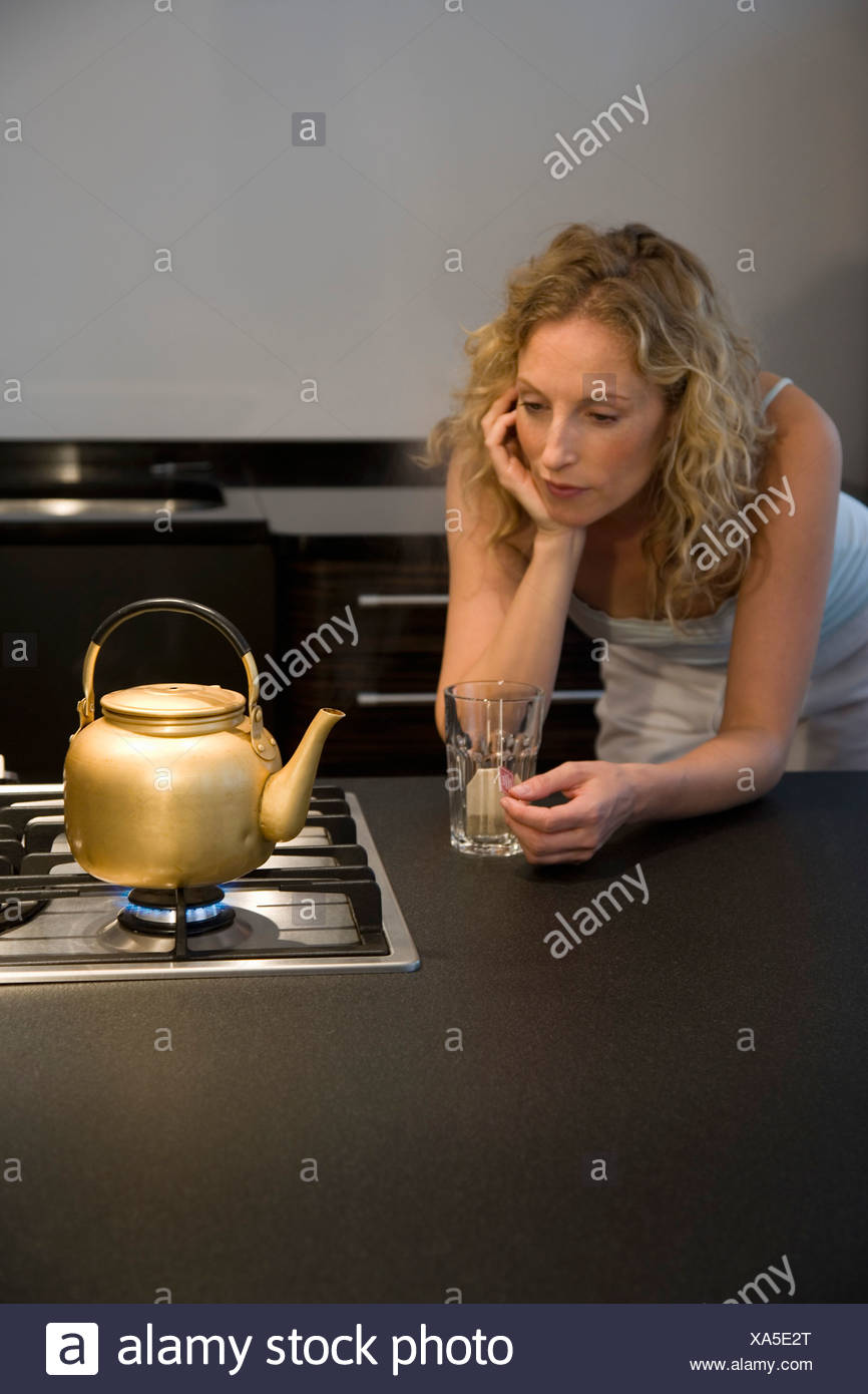 A woman waiting for a kettle to boil - Stock Image
