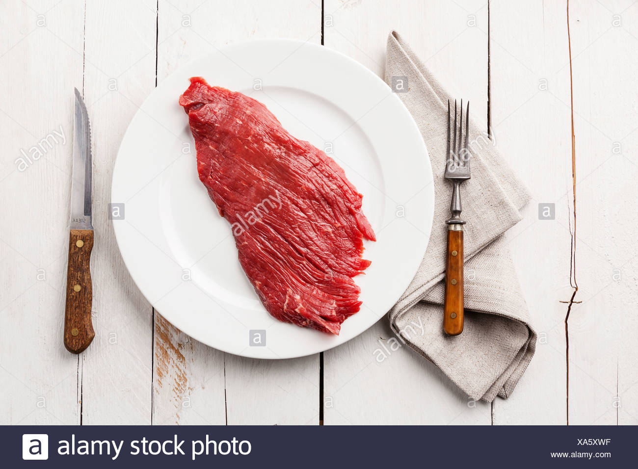 Prime cut of beef steak on plate on white wooden background - Stock Image