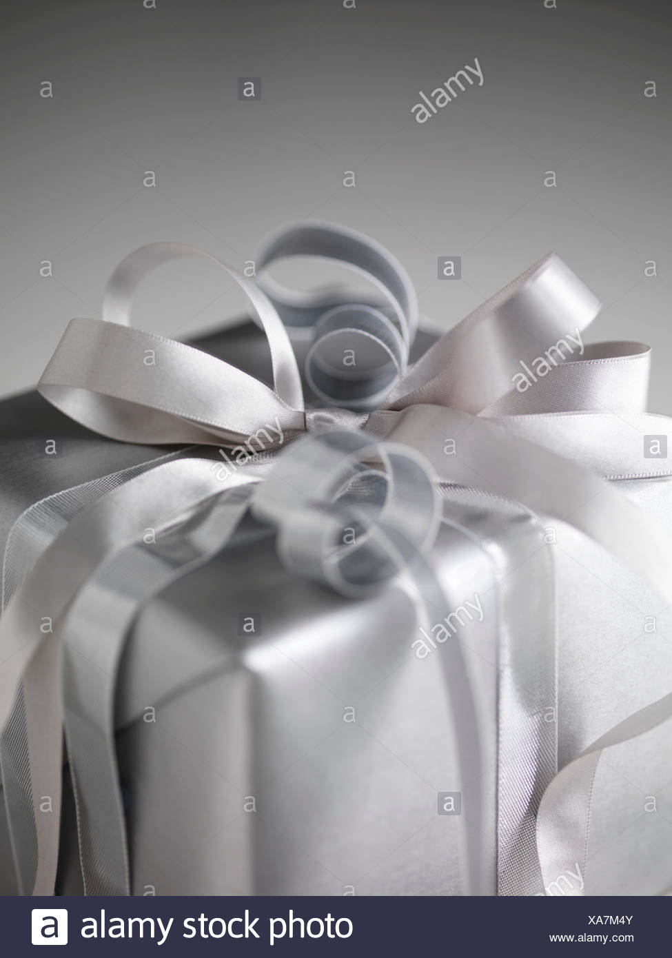 Still life with parcel wrapped in silver paper and ribbons - Stock Image