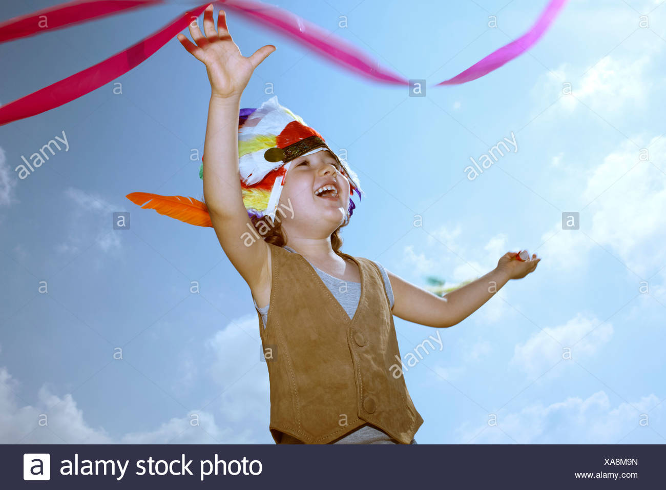 Toddler in Indian headdress with ribbon - Stock Image