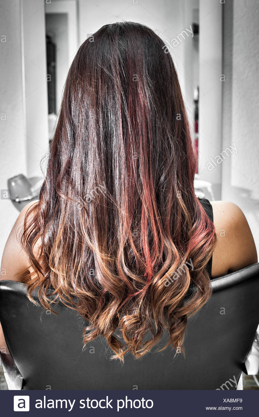 Rear view of young woman in hair salon with long brunette hair with waves and pink highlights - Stock Image