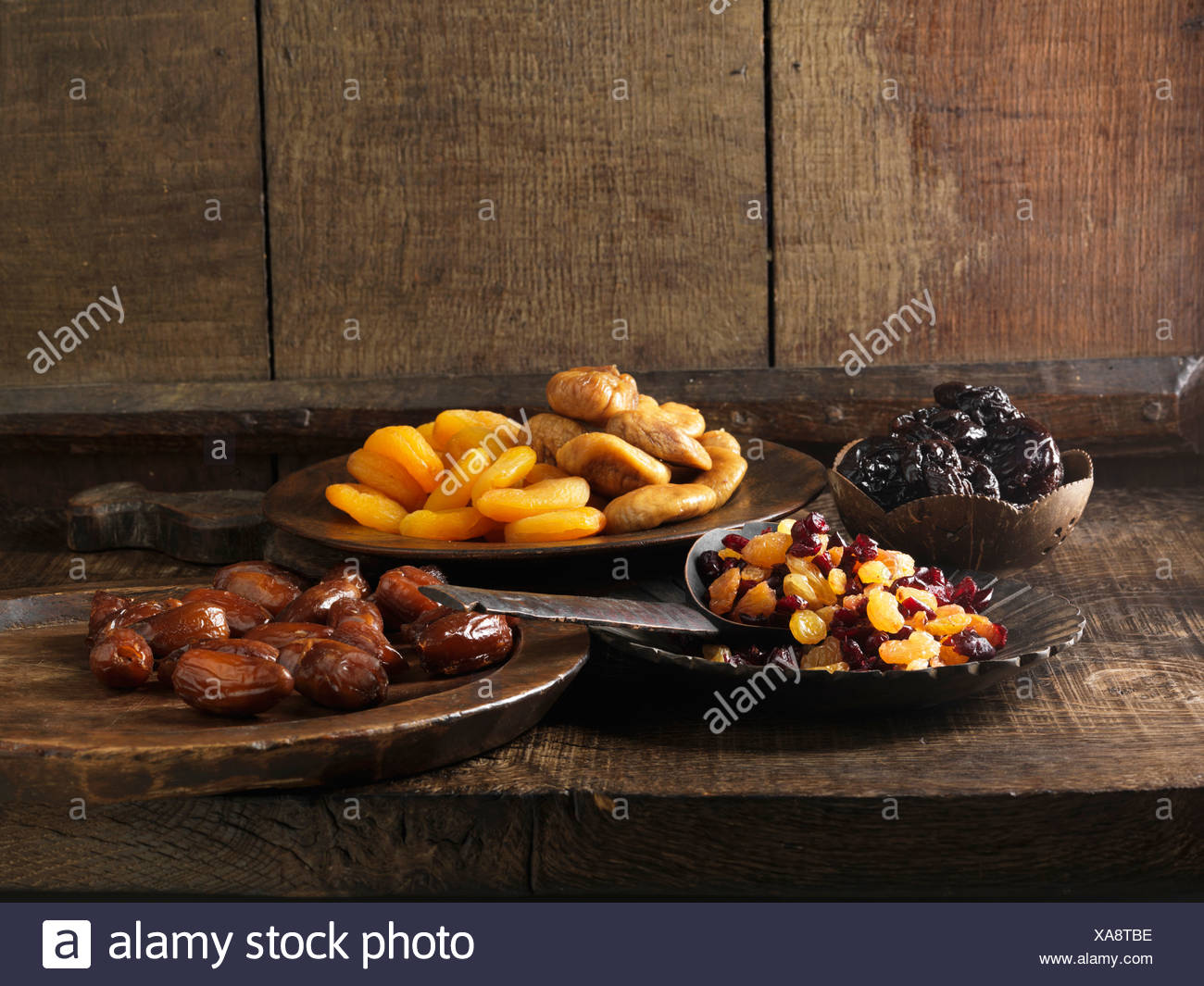 Dried fruits on assorted serving plates - Stock Image