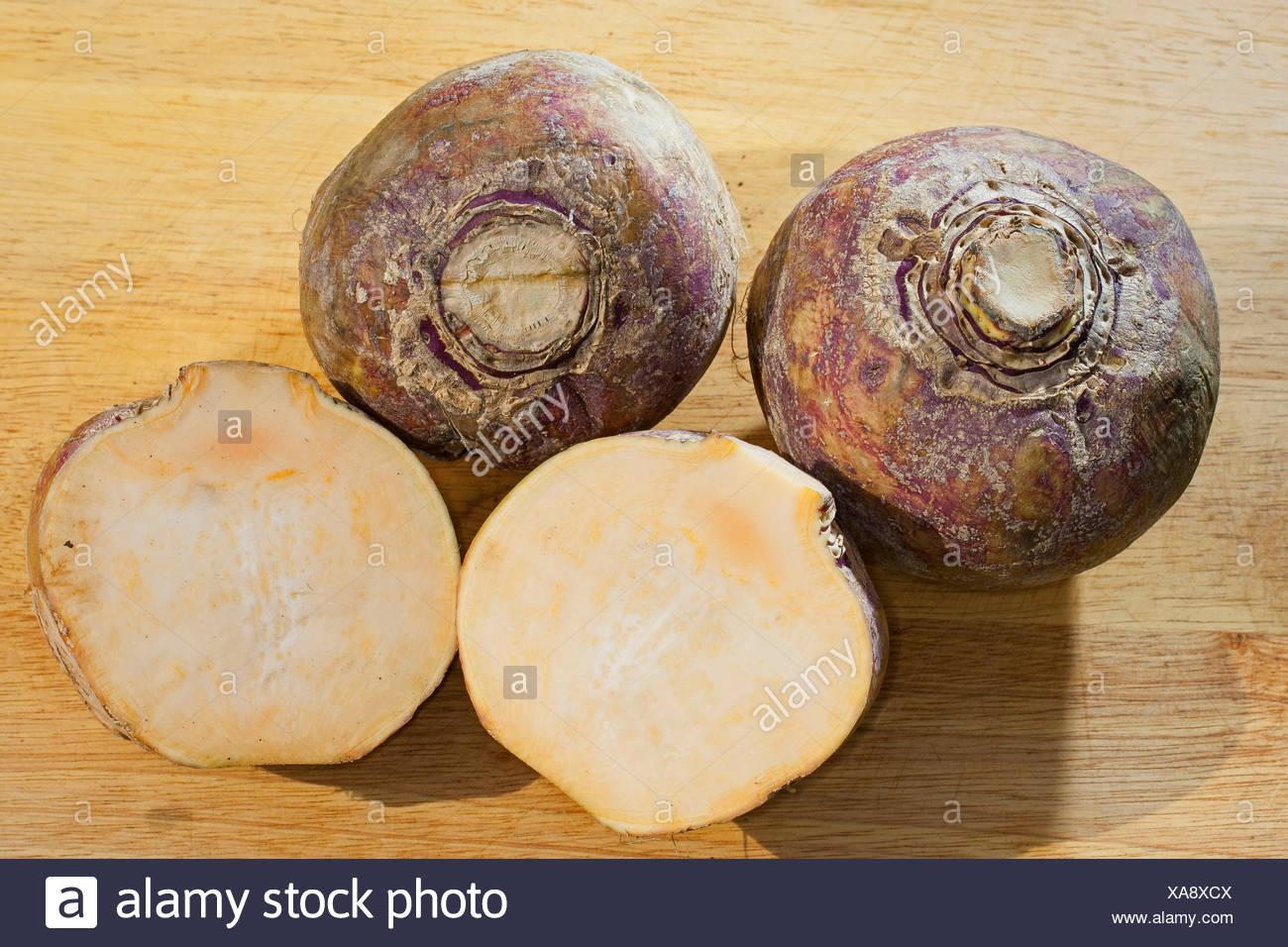 rutabaga, swede, turnip, yellow turnip, neep, root, beet (Brassica napus subsp. rapifera, Brassica napus rapifera, Brassica rapifera), three harvested rutabagas, one of them halved, Germany - Stock Image