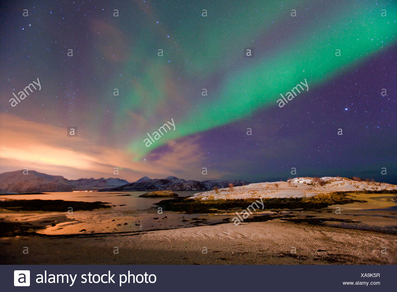 polar lights and red couds as light pollution above Tromso, Norway, Troms, Sommaroey - Stock Image