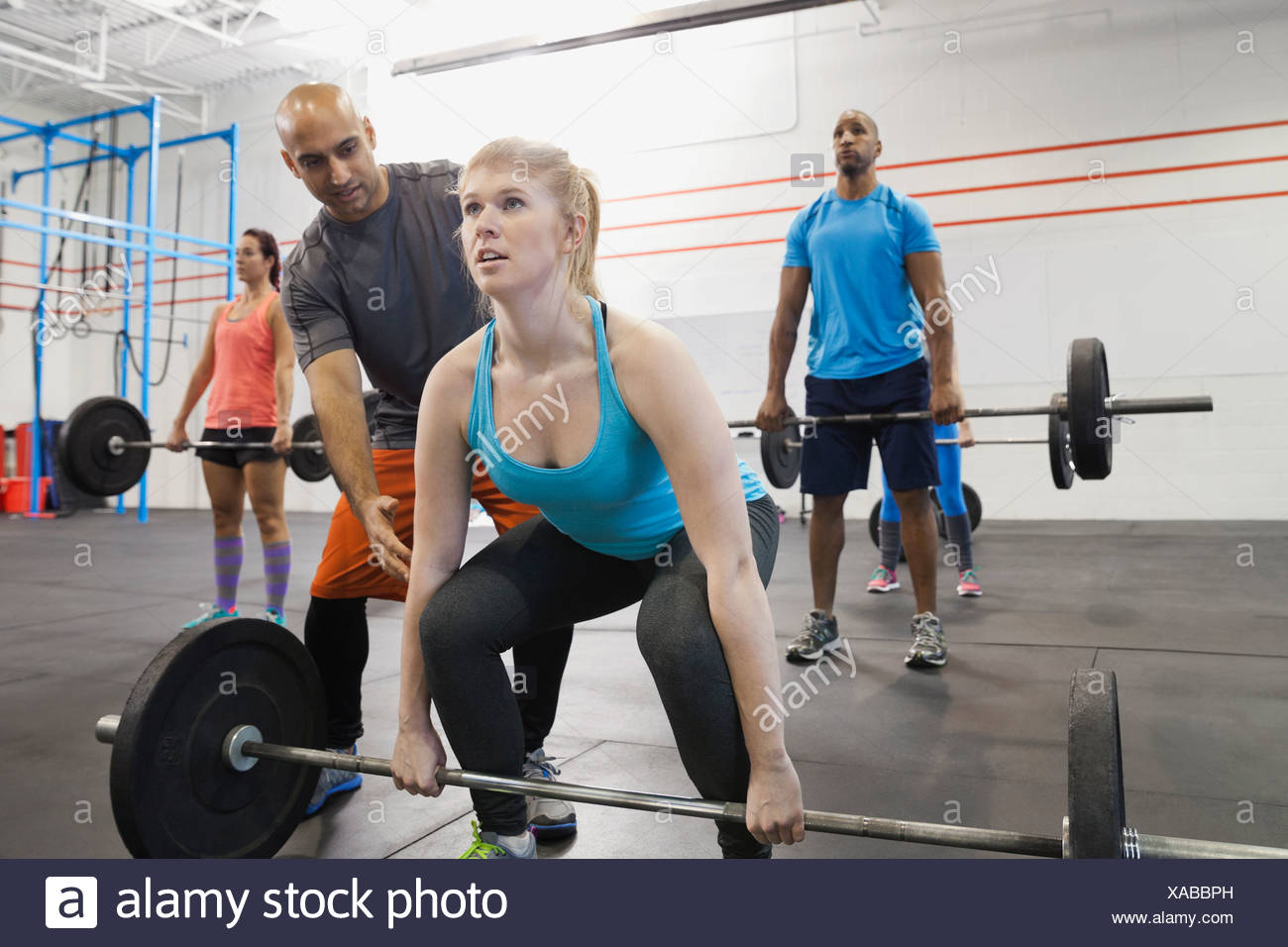 Gym instructor assisting woman with deadlift technique - Stock Image