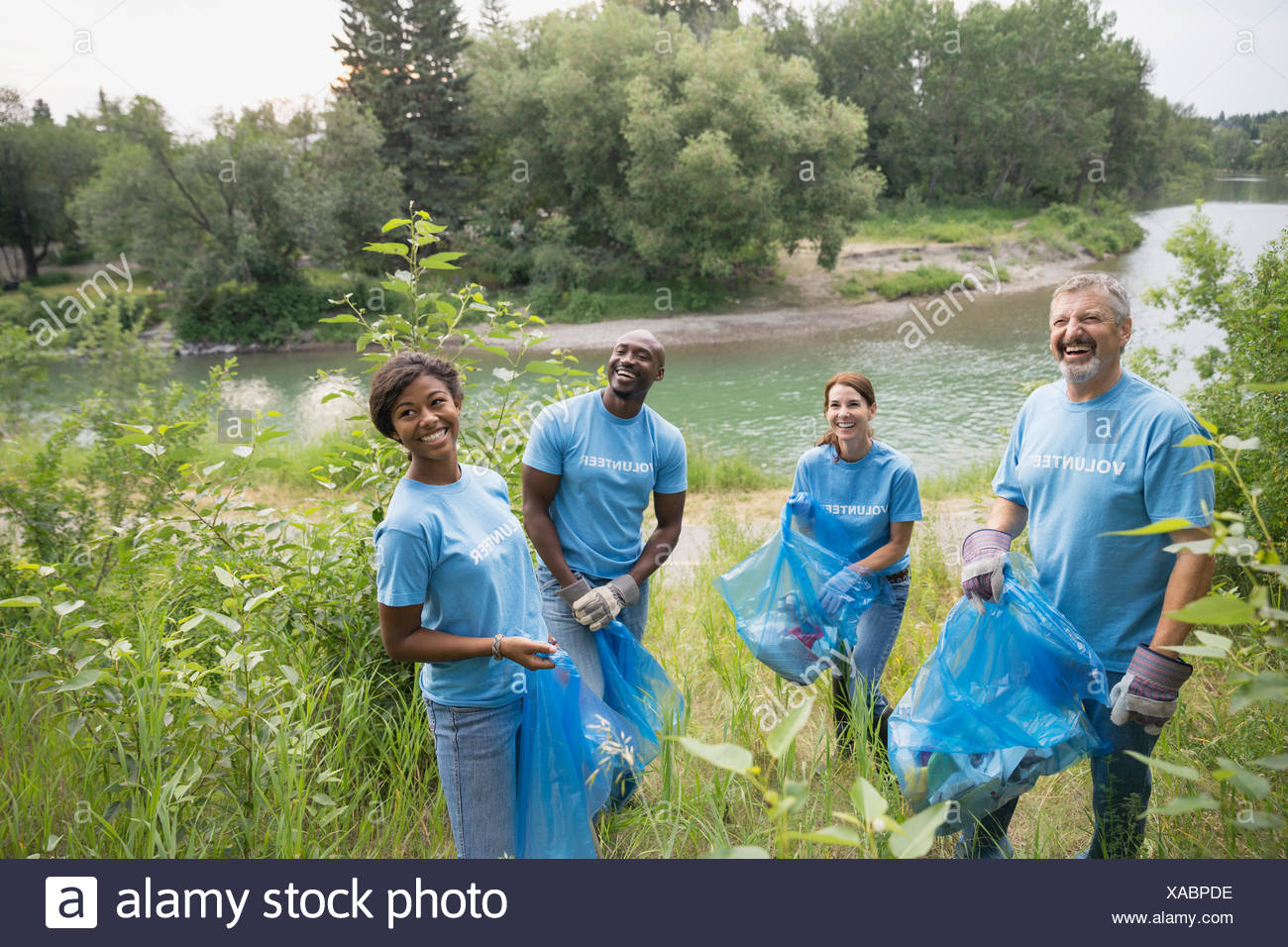 Portrait of smiling volunteers with garbage bags - Stock Image