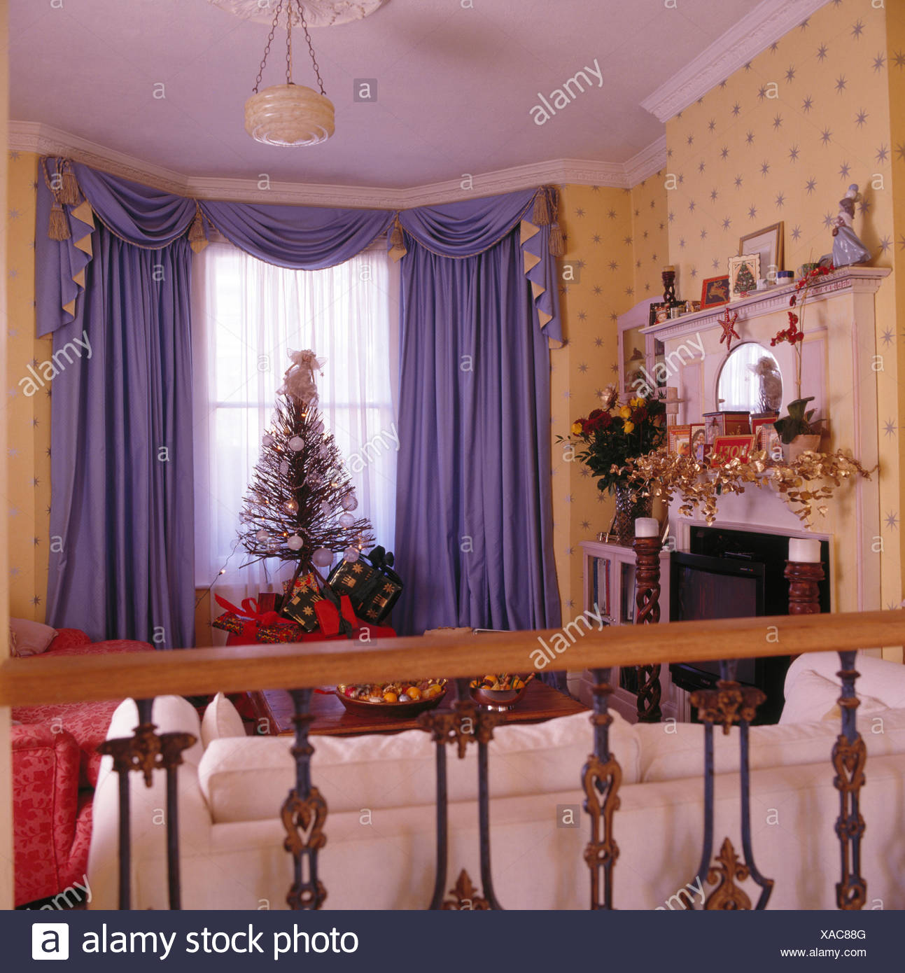 Purple Swagged And Tailed Curtains In Nineties Living Room Decorated For  Christmas