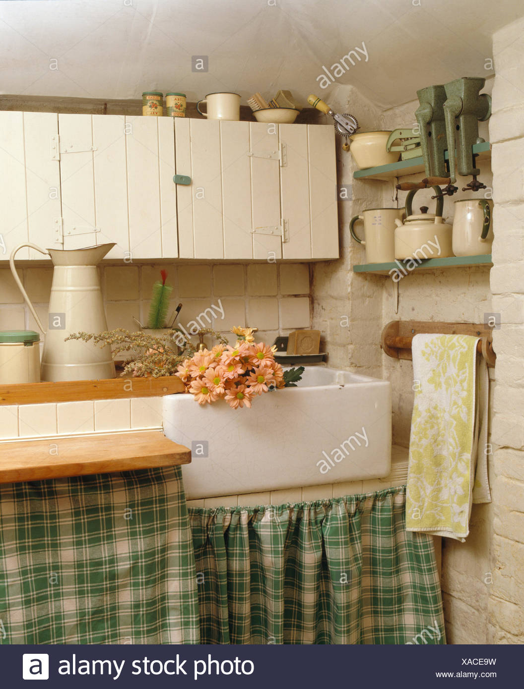Peach Pink Daisies In Belfast Sink In Fitted Unit With Green Checked  Curtains In Economy Style Cottage Kitchen
