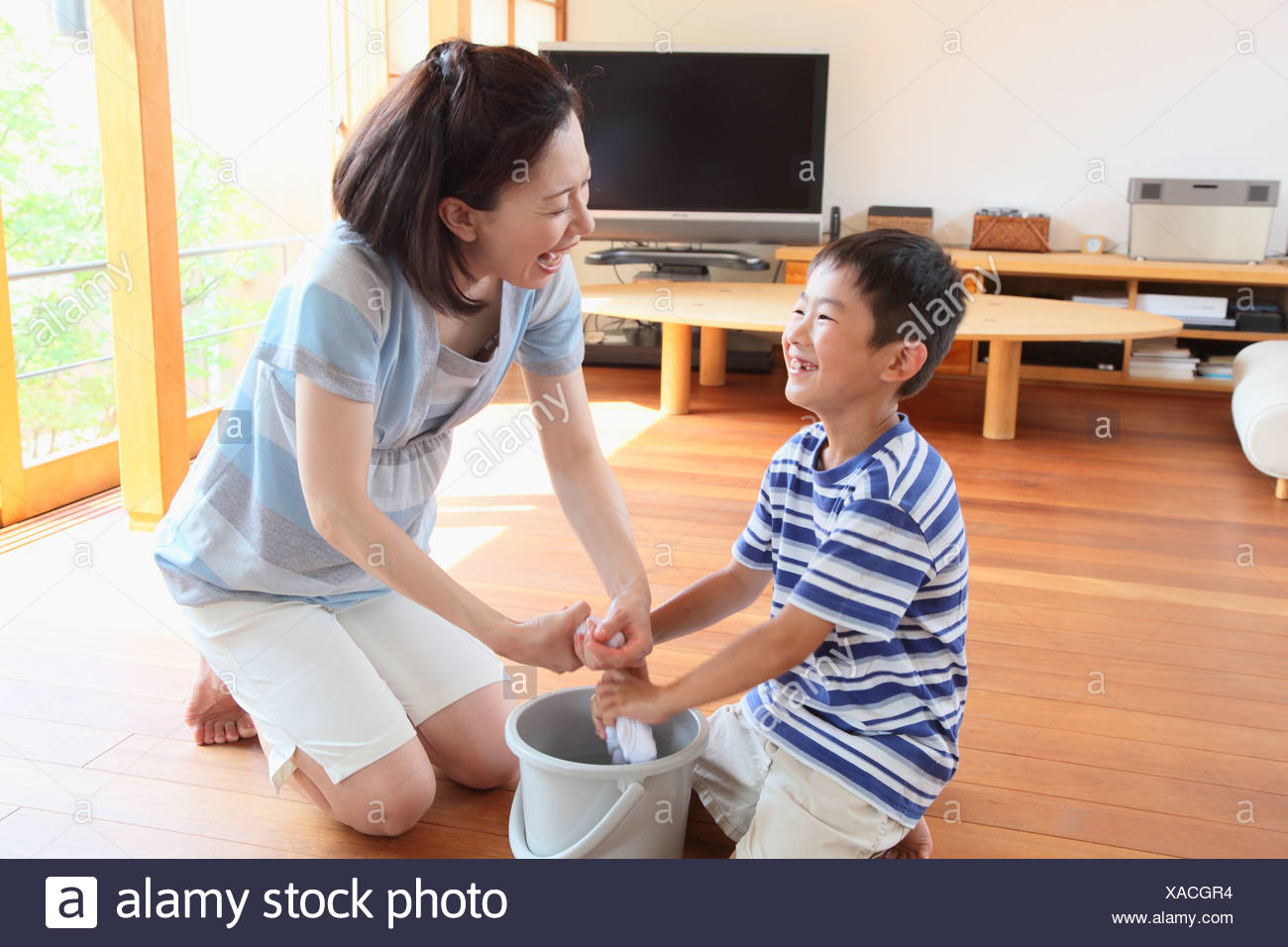 Mother and boy Squeezing dust cloth - Stock Image