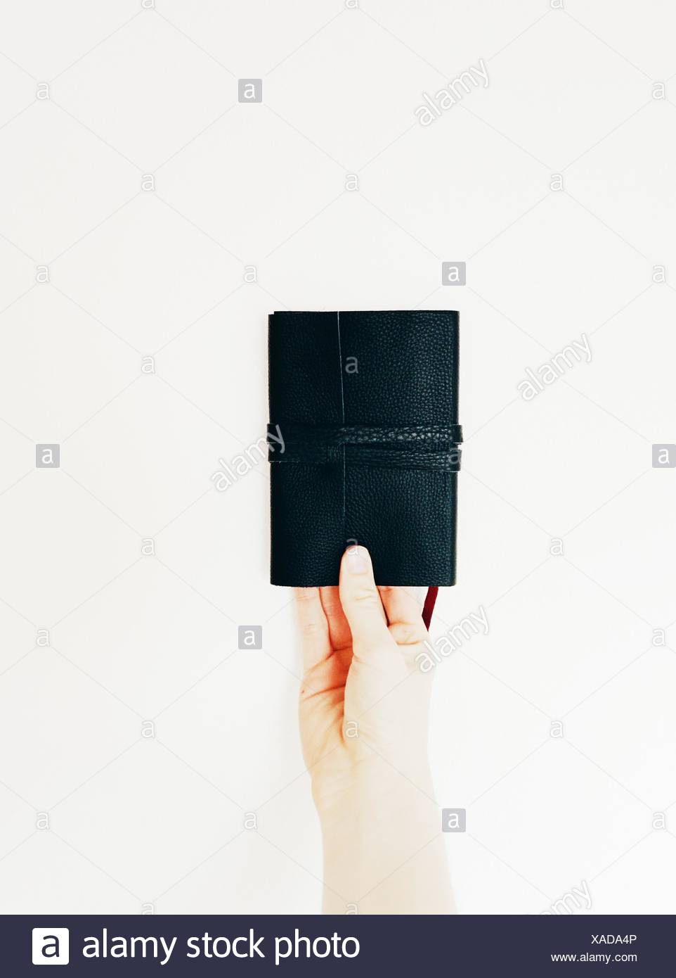 Close-Up Of Hand Holding Black Wallet Over White Background - Stock Image